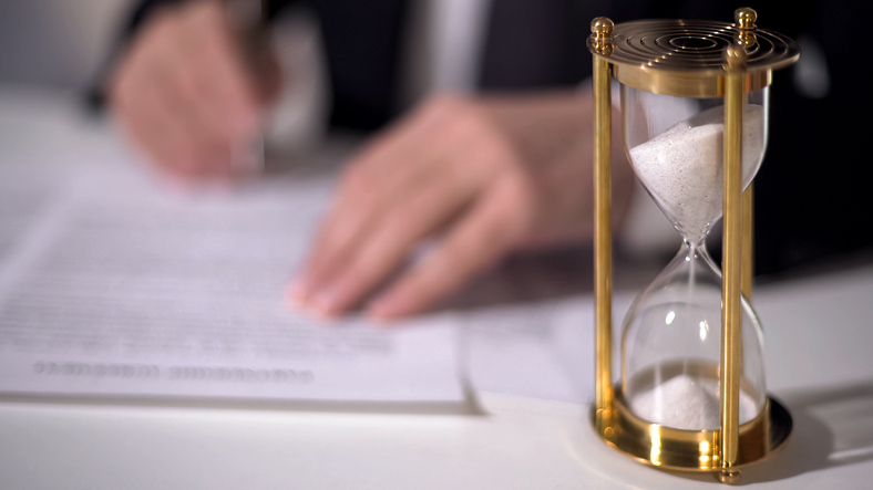 Stephen C. Carter, PC Attorney at Law | Hartwell, GA | closeup of sand clock measuring time as signing important documents